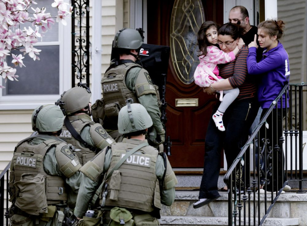 In this April 19, 2013, file photo, a woman carries a girl from their home as a SWAT team searching for a suspect in the Boston Marathon bombings enters the building in Watertown, Mass.  (AP)