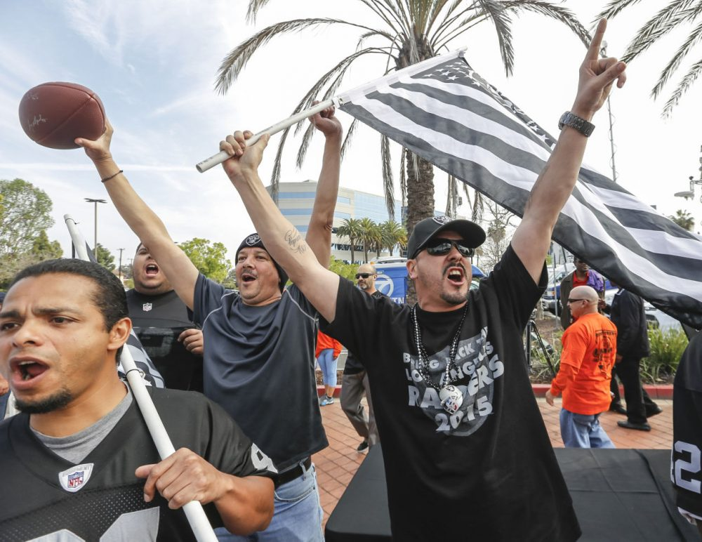 Raiders fan Sergio Gutierrez, right, joins football fans celebrating a proposed NFL football stadium by the owners of the San Diego Chargers and Oakland Raiders, during a news conference in Carson, Calif. (Damian Dovarganes/AP)