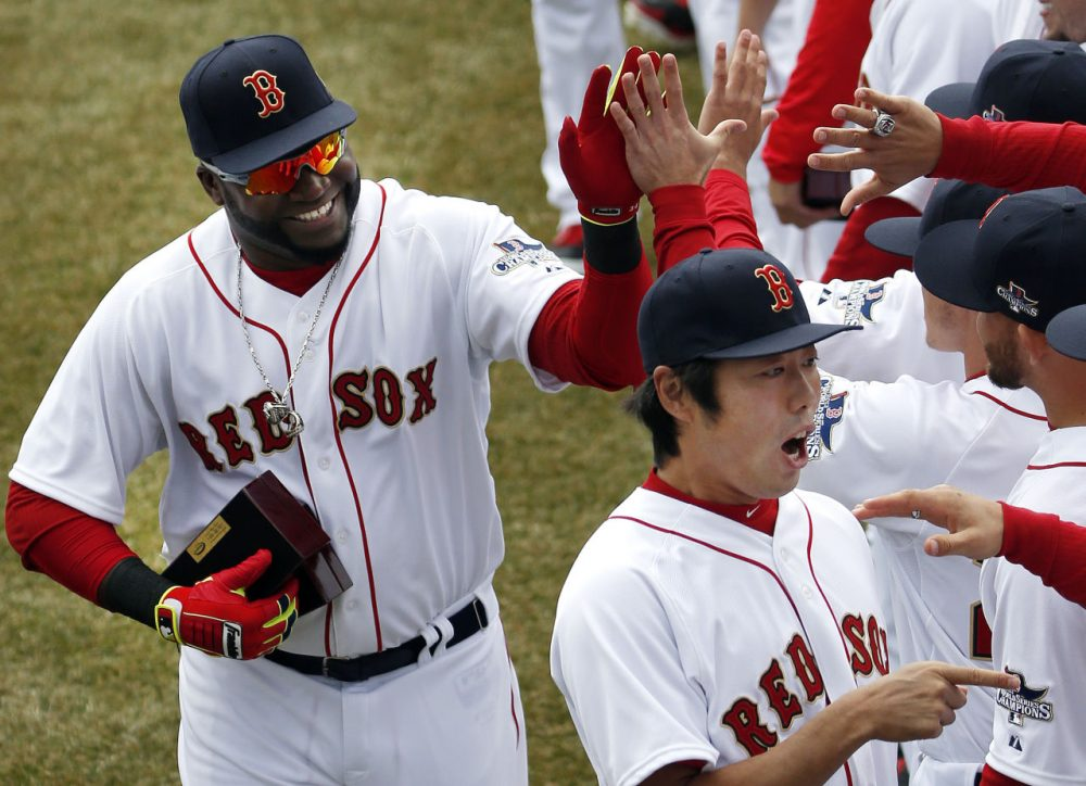 Boston Red Sox designated hitter David Ortiz, left, and relief pitcher Koji Uehara, lower right, celebrate with teammates after receiving their 2013 World Series rings at Fenway Park in Boston, Friday, April 4, 2014. (AP/Elise Amendola)