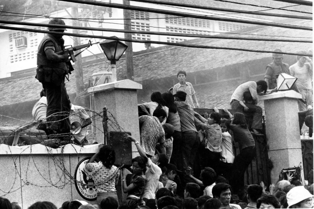 In this April 29, 1975, file photo, mobs of Vietnamese people scale the wall of the U.S. Embassy in Saigon, trying to get to a helicopter pickup zone. (Neal Ulevich/AP)