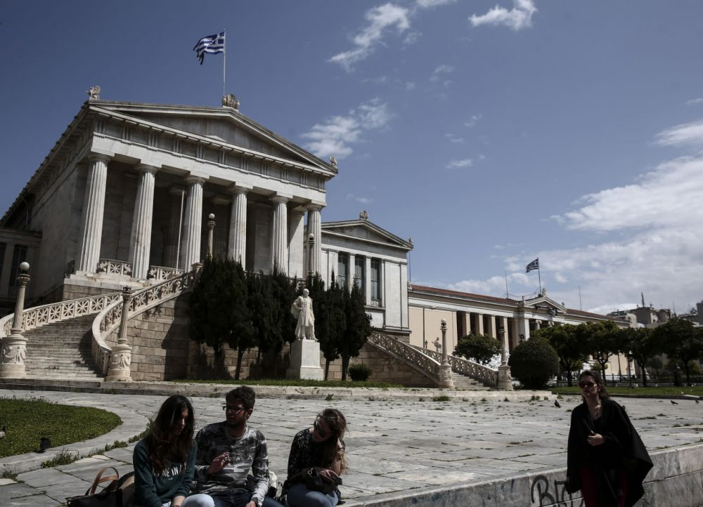 Young people sit in front of the National Library of Athens on Monday, April 6. Greece and its international creditors are still struggling to agree on a list of economic reforms that are deemed necessary for the country to unlock emergency funds. (Yorgos Karahalis/AP)