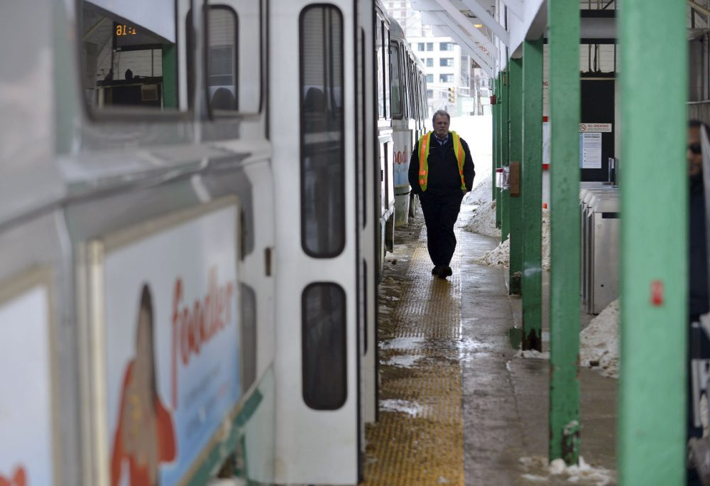 An MBTA Employee walks along the platform next to an idle transit train at the Leachmere T station in Cambridge on Feb. 10, 2015. (Josh Reynolds/AP)