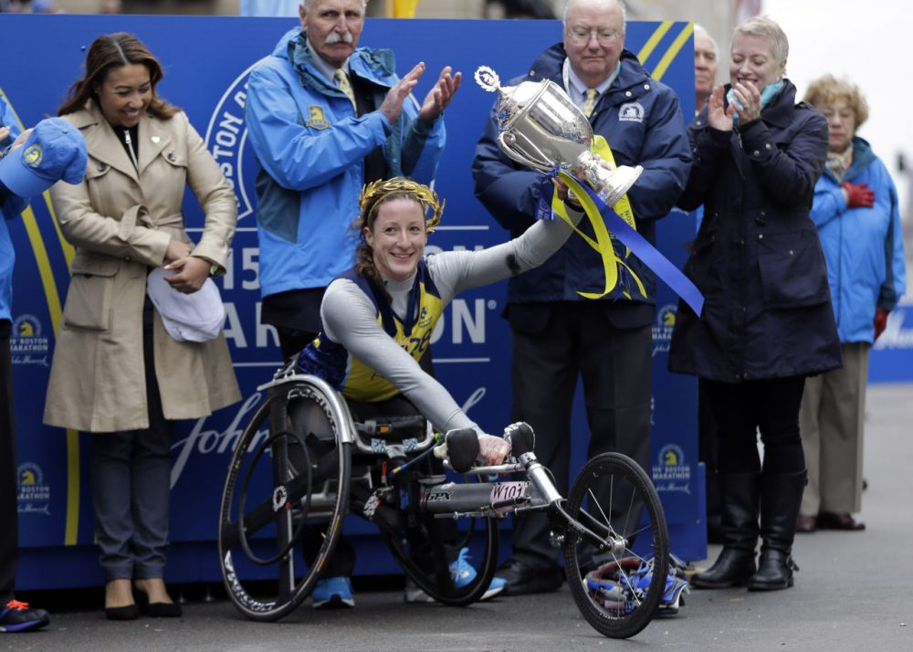 Tatyana McFadden  hoists her trophy after winning the women's wheelchair division. (Elise Amendola/AP)
