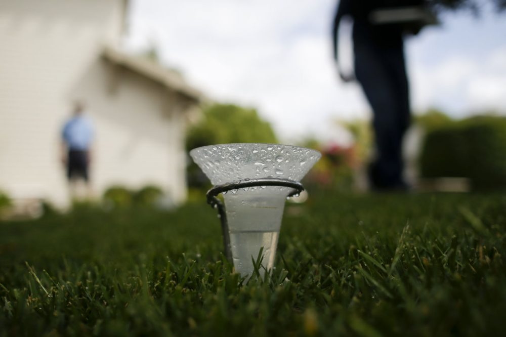"""A water conservationist for San Diego County Water Authority checks sprinkler flow on his lawn as part of the county's """"Watersmart Checkup"""" Wednesday in Carlsbad, Calif. State regulators recently ordered communities to slash water use anywhere from 8 to 36 percent. (Gregory Bull/AP)"""