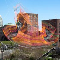 Janet Elchelman's 2,000-pound fiber net sculpture  is suspended between three skyscrapers and looks like it's floating high above the Rose Kennedy Greenway. (Robin Lubbock/WBUR)