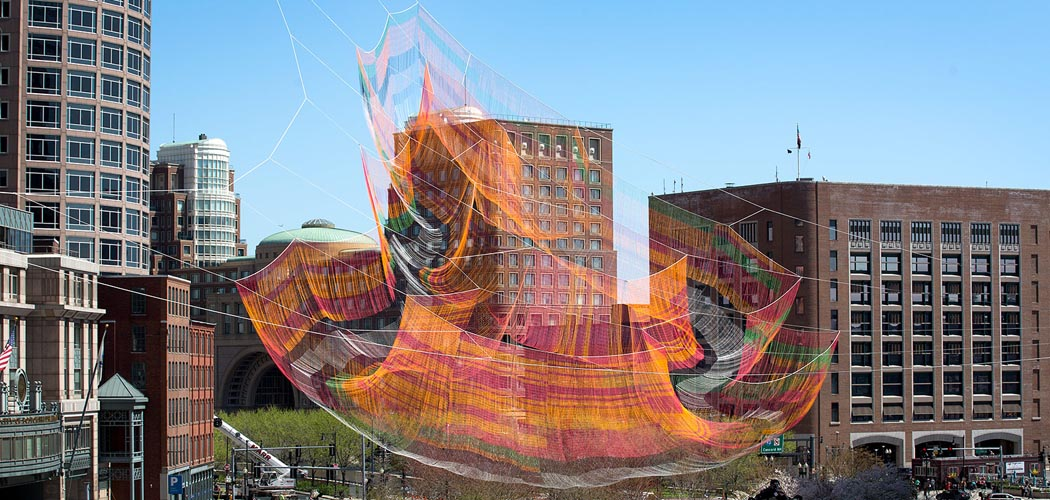 Janet Echelman's 2,000-pound fiber net sculpture  is suspended between three skyscrapers and looks like it's floating high above the Rose Kennedy Greenway. (Robin Lubbock/WBUR)