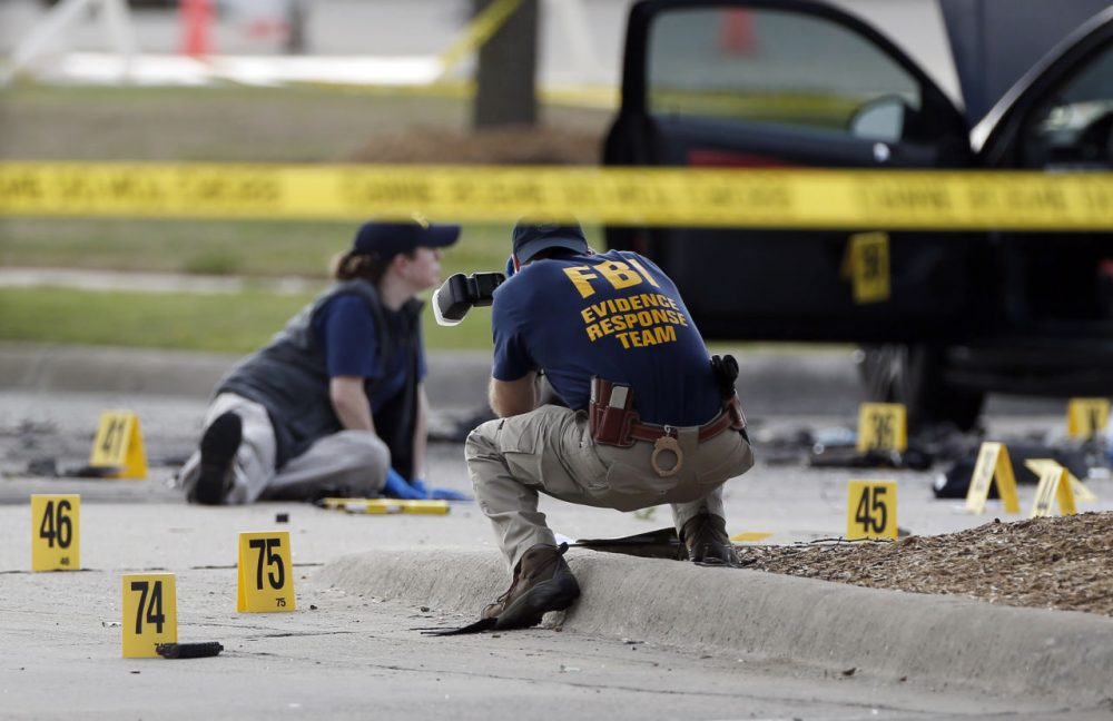 FBI crime scene investigators document the area around two deceased gunmen and their vehicle outside the Curtis Culwell Center in Garland, Texas, Monday, May 4, 2015. Police shot and killed the men after they opened fire on a security officer outside the suburban Dallas venue, which was hosting provocative contest for Prophet Muhammad cartoons Sunday night, authorities said. (Brandon Wade/AP)
