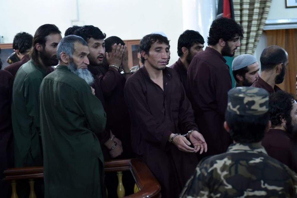 An Afghan security personnel escorts suspects at close of daily proceedings at the Primary Court trial in Kabul on May 2, 2015. The first trial of 49 suspects, including 19 police officers, on charges relating to the mob killing of an Afghan woman began in Kabul on May 2 and is expected to continue for two days. The suspects all face charges relating to the March 19 killing of a 27-year-old woman, Farkhunda. (Wakil Kohsar/AFP/Getty Images)