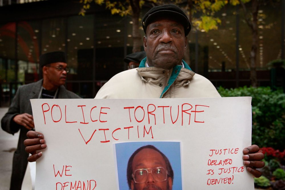 Aaron Cheney demonstrates outside the federal courthouse where former Chicago Police Commander Jon Burge was attending a hearing on charges he obstructed justice and committed perjury for lying while under oath during a 2003 civil trial about decades-old Chicago police torture allegations October 27, 2008 in Chicago, Illinois. Burge could not be charged for the torture of suspects because the federal statute of limitations for the crime had expired. (Scott Olson/Getty Images)