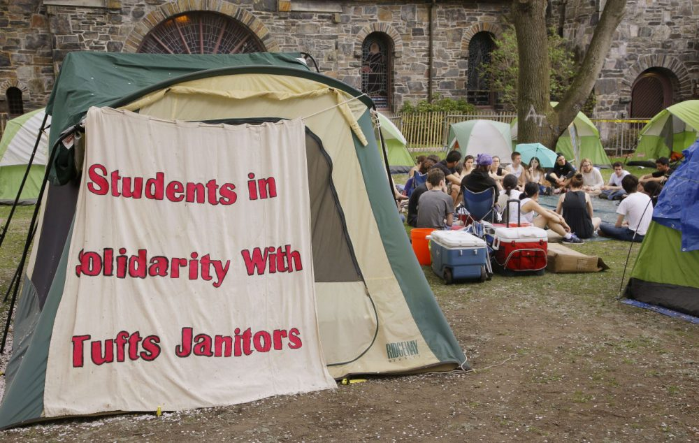 On Tuesday, Tufts University students hold a meeting in a campsite next to the school's administration building, where students have been protesting the university's plans to cut janitorial jobs. (Stephan Savoia/AP)