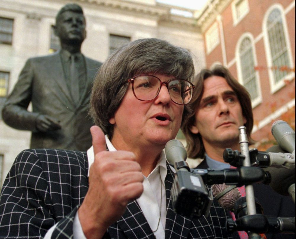 Death penalty opponent Sister Helen Prejean addresses members of the media as fellow opponent Paul Hill looks on while standing in front of a statue of President John F. Kennedy, behind, outside the Statehouse in Boston in 1997. (Kuni/AP)