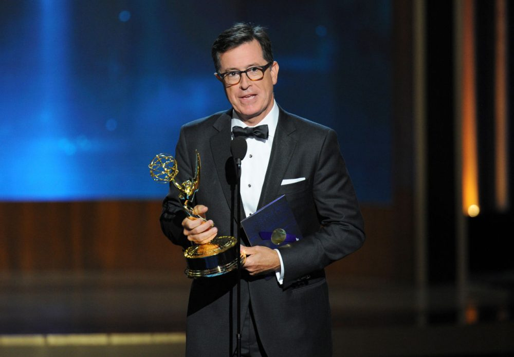 "Stephen Colbert  accepts the award for outstanding supporting actor in a miniseries or a movie on behalf of Martin Freeman for his work on ""Sherlock: His Last Vow (Masterpiece)"" at the 66th Primetime Emmy Awards. (Vince Bucci/Invision for the Television Academy/AP)"