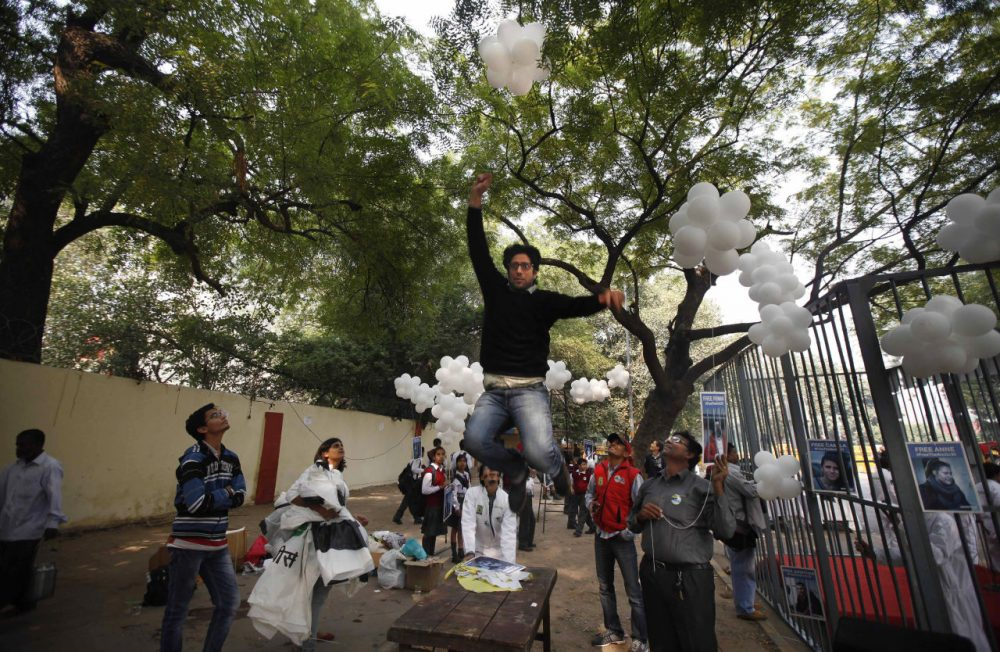In this 2013 photo, a Greenpeace activist jumps to catch a thread tied to balloons during a protest in India. The nation is cracking down on foreign-funded charities lately. (Altaf Qadri/AP)