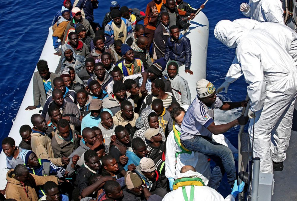 "In this photo from April 22, 2015, migrants crowd and inflatable dinghy as rescue vassel "" Denaro "" of the Italian Coast Guard approaches them, off the Libyan coast, in the Mediterranean Sea. (Alessandro Di Meo/ANSA via AP)"