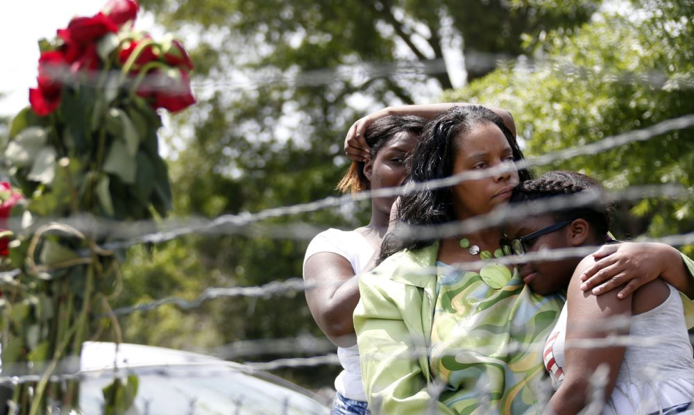 Area residents Alberta Harris, center, and Waynetta Theodore, left, and Christiena Preston, console each other as they pay their respects at a makeshift memorial, near the site where two Mississippi police officers were killed, Sunday, May 10, 2015, in Hattiesburg, Miss. (Rogelio V. Solis/AP)