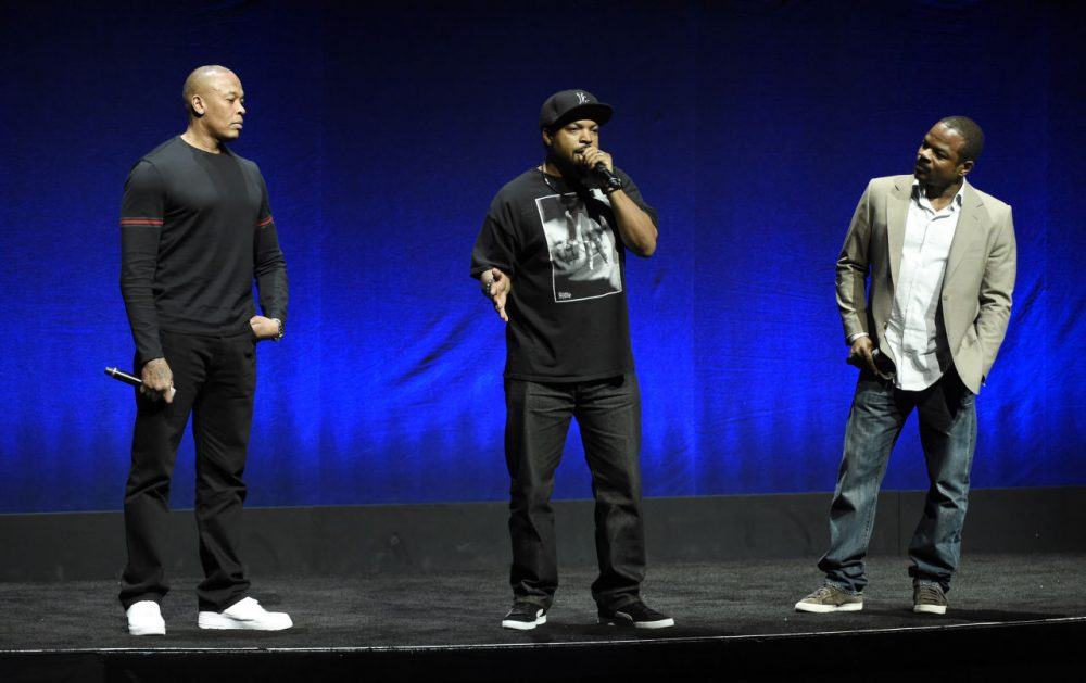 "N.W.A. members Dr. Dre, left, and Ice Cube, center, two of the subjects of the upcoming biographical drama ""Straight Outta Compton,"" discuss the film with director F. Gary Gray during the Universal Pictures presentation at CinemaCon 2015 in April. (Chris Pizzello/Invision/AP)"