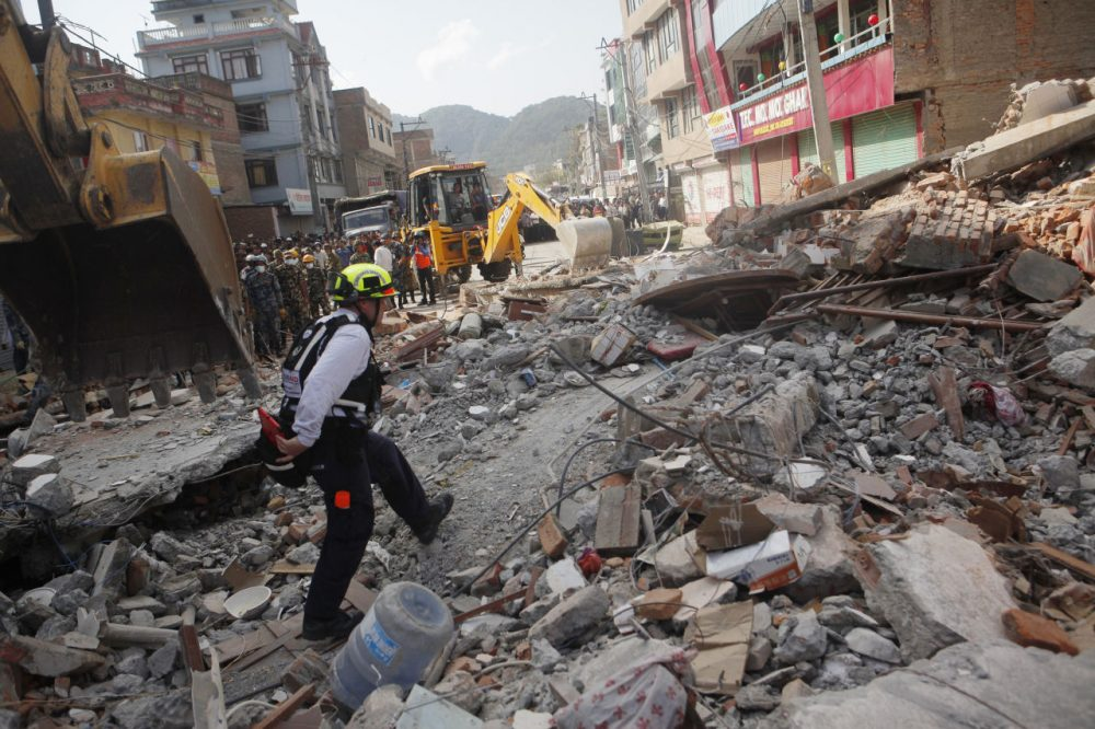 A rescue worker from USAID inspects the site of a building that collapsed in an earthquake in Kathmandu, Nepal, Tuesday, May 12, 2015. A major earthquake has hit Nepal near the Chinese border between the capital of Kathmandu and Mount Everest less than three weeks after the country was devastated by a quake. (Niranjan Shrestha/AP)