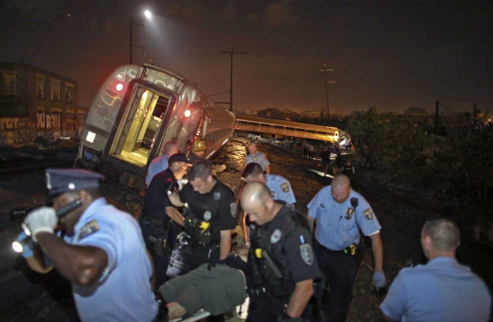 Emergency personnel work the scene of a train wreck, Tuesday, May 12, 2015, in Philadelphia. An Amtrak train headed to New York City derailed and crashed in Philadelphia. (Joseph Kaczmarek/AP)