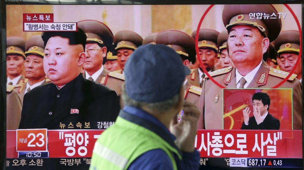 """A man watches a TV news program reporting that People's Armed Forces Minister Hyon Yong Chol was killed by anti-aircraft gunfire, at Seoul Railway Station in Seoul, South Korea, Wednesday, May 13, 2015. North Korean leader Kim Jong Un executed his defense chief for sleeping during a meeting and talking back to the young leader, South Korea's spy agency told lawmakers Wednesday, citing what it called credible information. The part of letters on the bottom """"Pyongyang, executed by anti-aircraft gunfire."""" (Lee Jin-man/AP)"""