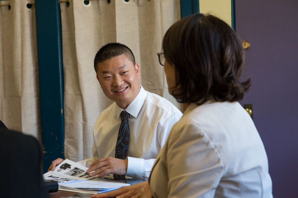 Incoming Superintendent Tommy Chang listens to the Boston International High School headmaster Nicole Bahnam on Wednesday. (Jesse Costa/WBUR)