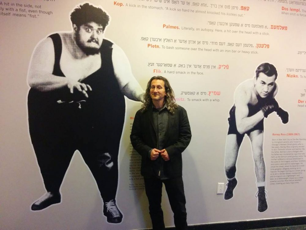 "Eddy Portnoy poses with the exhibit he curated on Yiddish street fighting as well as Jewish wrestlers in Europe and the U.S. including Martin Levy (left), who weighed in at over 600 pounds and was aptly nicknamed, ""The Blimp."""