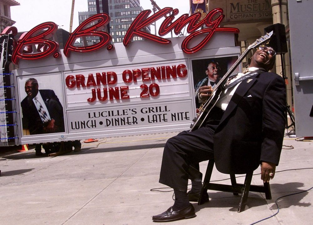 """Blues legend B.B. King, holding his guitar """"Lucille,"""" reacts as the neon sign for his New York restaurant and club arrives in Times Square, in May 2000. (Richard Drew/AP)"""