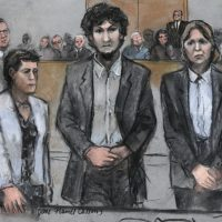 In this courtroom sketch, Boston Marathon bomber Dzhokhar Tsarnaev, center, stands with his defense attorneys as a death by lethal injection sentence is read at the Moakley Federal court house in the penalty phase of his trial in Boston, Friday, May 15, 2015. The federal jury ruled that the 21-year-old Tsarnaev should be sentenced to death for his role in the deadly 2013 attack. (Jane Flavell Collins/AP)