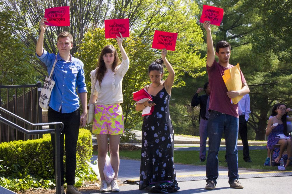 Students hold signs in support of janitorial staff at Tufts University's commencement on May 17, 2015.(Peter Balonon-Rosen/WBUR)