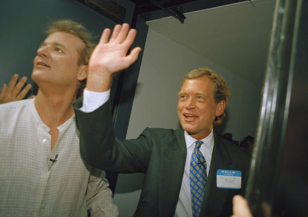 """In this Aug. 30, 1993 file photo, David Letterman, right, and Bill Murray wave from the side door of the Ed Sullivan Theater during the first episode of """"Late Show with David Letterman"""" in New York. After 33 years in late night and 22 years hosting CBS' """"Late Show,"""" Letterman will retire on May 20. (Jim Cooper/AP)"""