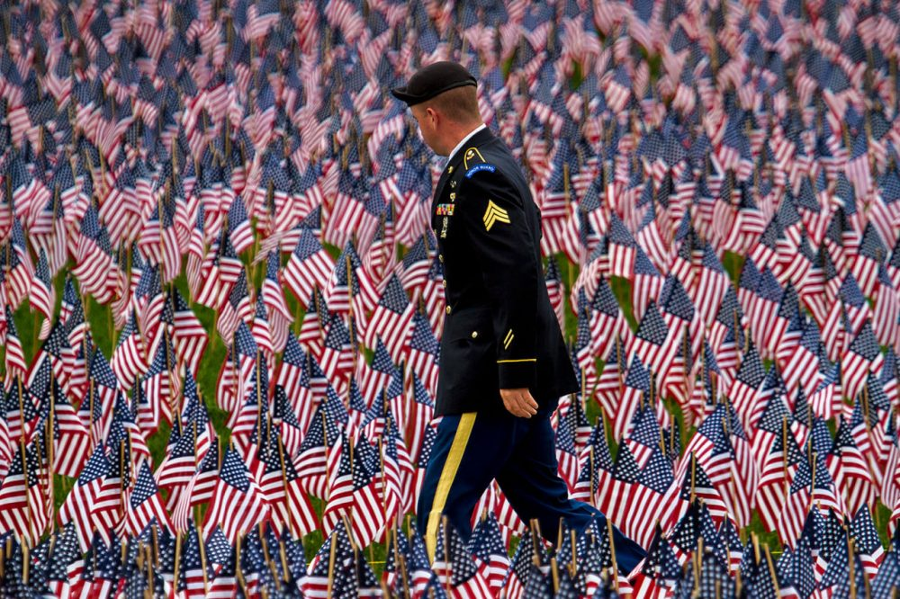 A soldier walks down a path looking at the 37,000 flags planted in the Boston common by the Massachusetts Military Heroes Fund. (Jesse Costa/WBUR)