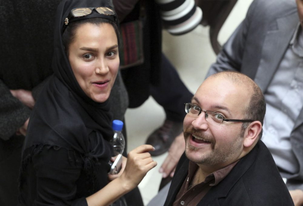 In this photo taken on April 11, 2013, Jason Rezaian, right, an Iranian-American correspondent for the Washington Post, and his wife Yeganeh Salehi, an Iranian correspondent for the Abu Dhabi-based daily newspaper The National, smile as they attend a presidential campaign of President Hassan Rouhani in Tehran, Iran. (Vahid Salemi/AP)