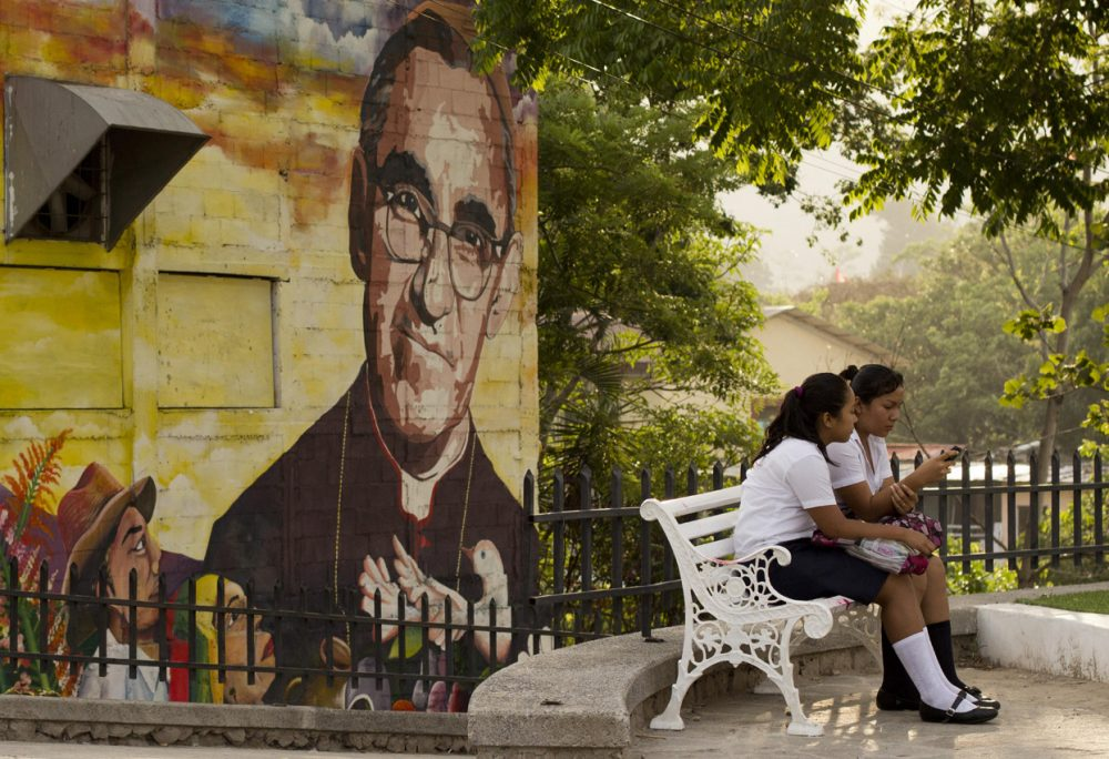 A mural of Roman Catholic Archbishop Oscar Romero decorates a wall where students sit in a plaza in Panchimalco, El Salvador, Thursday, May 21, 2015. (Salvador Melendez/AP)