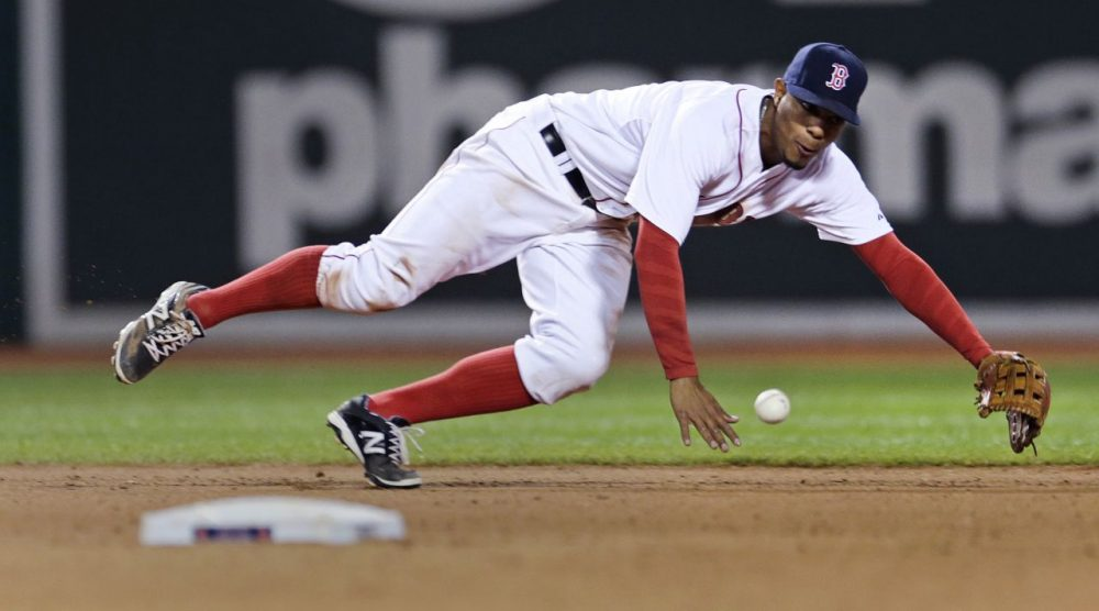 Red Sox shortstop Xander Bogaerts tries unsuccessfully to make a play on a single by Texas Rangers' Adam Rosales in the eighth inning of a game at Fenway, Thursday, May 21, 2015. (Charles Krupa/AP)