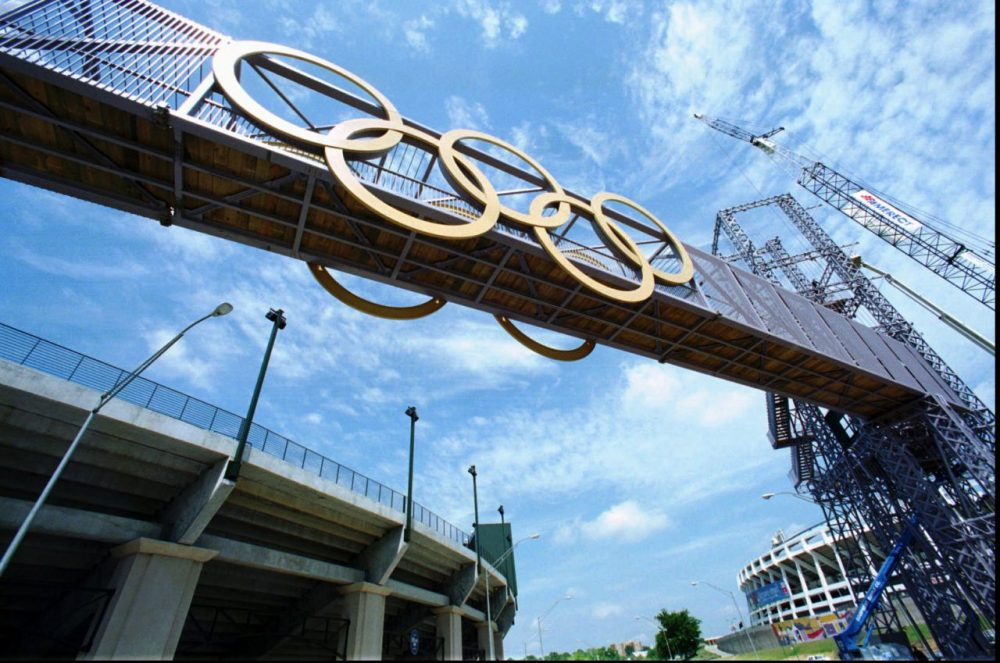 Olympic rings adorn both sides of the steel bridge that will span the space from the Centennial Olympic Stadium, left, to the Olympic Cauldron as construction continues at the site in downtown Atlanta in 1996. (Ric Feld/AP)