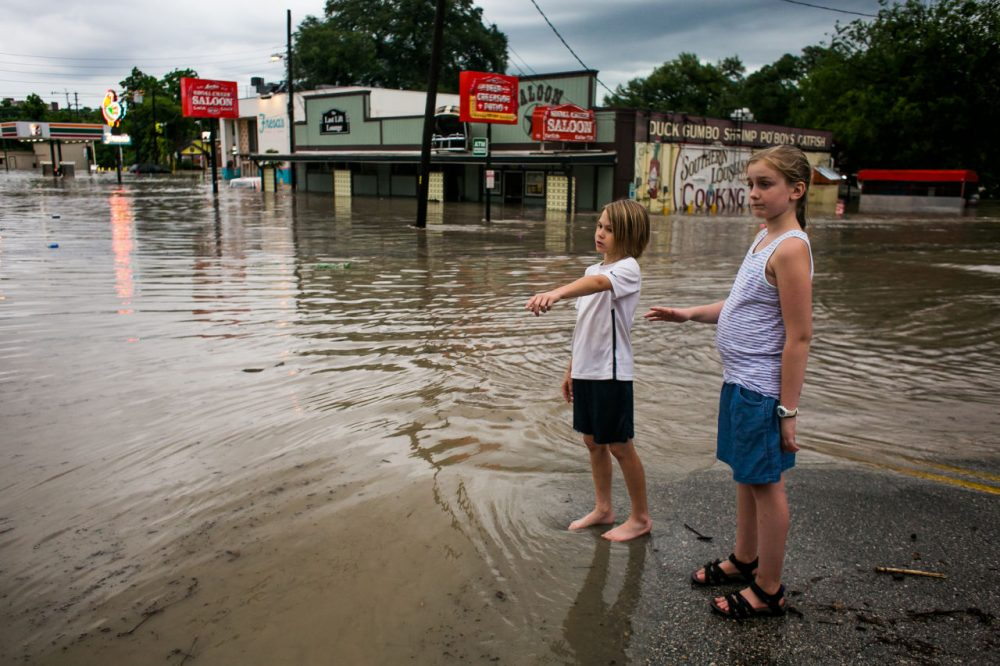 Murphy Canning and Annika Rolston watch as a street remains underwater from days of heavy rain on May 25, 2015 in Austin, Texas. Texas Gov. Greg Abbott toured the damage zone where one person is confirmed dead and at least 12 others missing in flooding along the Rio Blanco, which reports say rose as much as 40 feet in places, caused by more than 10 inches of rain over a four-day period. The governor earlier declared a state of emergency in 24 Texas counties. (Drew Anthony Smith/Getty Images)