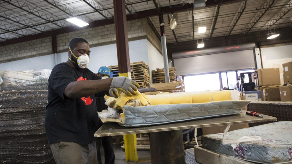 Andre Williams, a worker at Park City Green in Bridgeport, deconstructs a mattress. (Ryan King/WNPR)