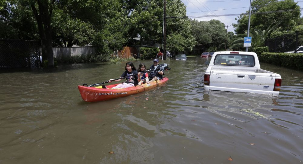 Domingo Molina, right, paddles with his granddaughters Crystal, left, and Alicia, center, down a flooded street in Houston, Tuesday, May 26, 2015. Heavy rain overnight caused flooding and closure of sections of highways in the Houston area. (David J. Phillip/AP)