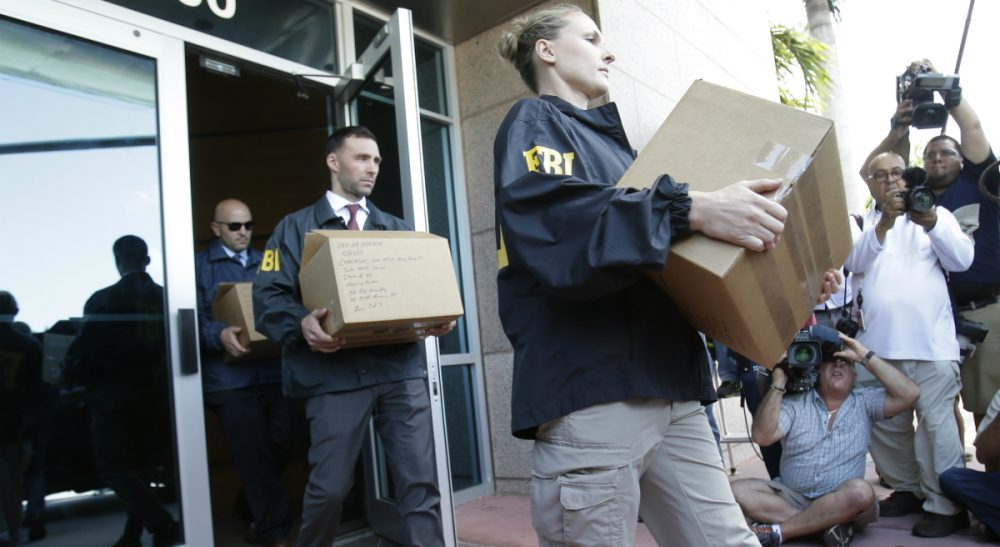 """Federal agents load a van with boxes of evidence taken from the headquarters of the Confederation of North, Central America and Caribbean Association Football (CONCACAF,) Wednesday, May 27, 2015, in Miami Beach, Fla. Swiss prosecutors opened criminal proceedings into FIFA's awarding of the 2018 and 2022 World Cups, only hours after seven soccer officials were arrested Wednesday pending extradition to the U.S. in a separate probe of """"rampant, systemic, and deep-rooted"""" corruption. (Wilfredo Lee/AP)"""