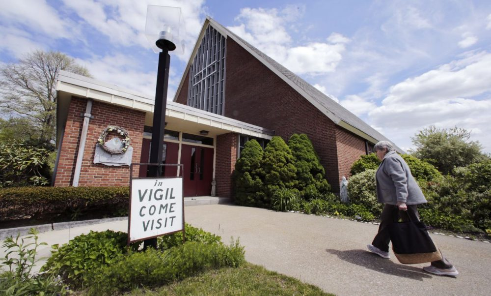 Barbara Nappa, of Scituate, Mass., heads into the St. Frances Xavier Cabrini Church to take her turn sitting vigil in Scituate, Mass. (Charles Krupa/AP)