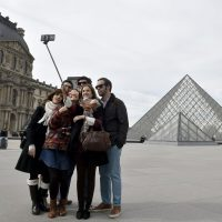 Tourists use a selfie-stick to take a picture of themselves in front of the Pyramid of the Louvre in Paris on March 7, 2015. (Dominique Faget/AFP/Getty Images)
