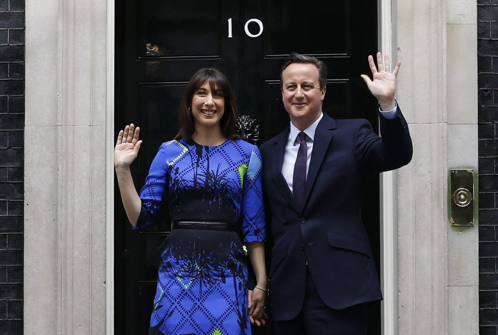 Britain's Prime Minister David Cameron and his wife Samantha wave from the steps of 10 Downing Street in London Friday, May 8, 2015 after meeting Britain's Queen Elizabeth II where he informed her that he has enough support to form a government. The Conservative Party swept to power Friday in Britain's Parliamentary elections winning an unexpected majority. (Kirsty Wigglesworth/AP)