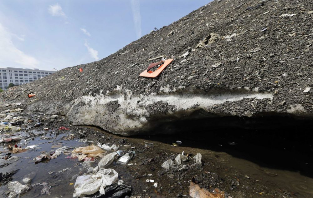 A 75-foot-high snow mound in the Seaport District has been reduced to a three-story pile of dirt and trash, including bicycles, traffic cones and even half a $5 bill, that remains encrusted in solid ice. Crews have been working for six weeks to clean away the trash as it breaks free from the mound. (Elise Amendola/AP)