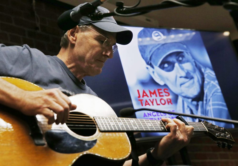 """James Taylor plays guitar during a news conference to promote his new song """"Angels of Fenway"""" before a baseball game between the Red Sox and the New York Yankees in Boston, Sunday, May 3, 2015. (AP/Michael Dwyer)"""
