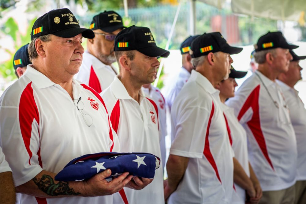 At a ceremony in Ho Chi Minh City Thursday, former Marine Security Guard John Ghilain, of Malden, holds a folded American flag in honor of one of the last two U.S. troops to die on Vietnamese soil, Cpl. Charlie McMahon, of Woburn. (Quinn Ryan Mattingly for WBUR)