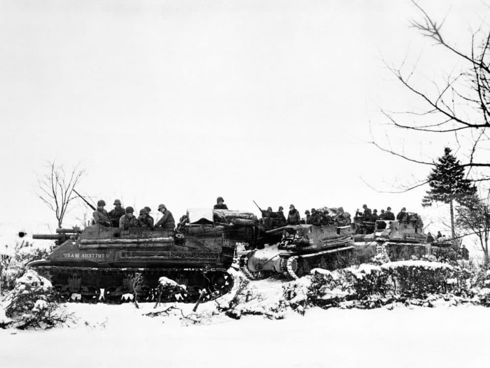 American tanks and armored gun carriers drive over snow-covered terrain towards Samree, Belgium Dec. 1944. (Fred Ramage/AP)