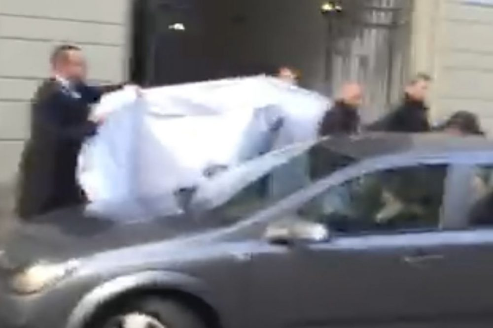 In this picture taken from a cell phone video, hotel employees hold a blanket to hide the identity of a person led out of a side entrance of the Baur au Lac hotel to a waiting car in Zurich, Switzerland, Wednesday, May 27, 2015. (AP)