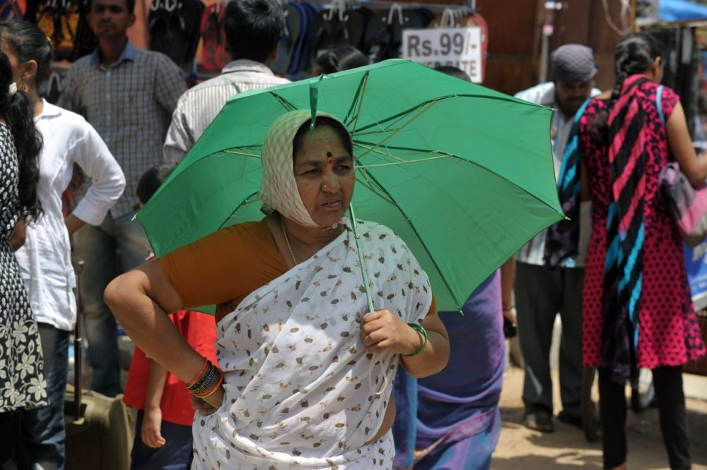 An Indian woman walks with an umbrella on a hot summer day in Hyderabad on May 26, 2015. (Noah Seelam/AFP/Getty Images)