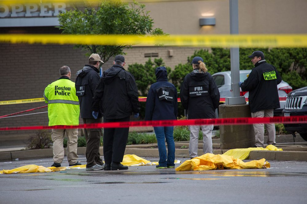 Authorities examine evidence at the scene of a fatal shooting Tuesday morning in Boston. (Jesse Costa/WBUR)