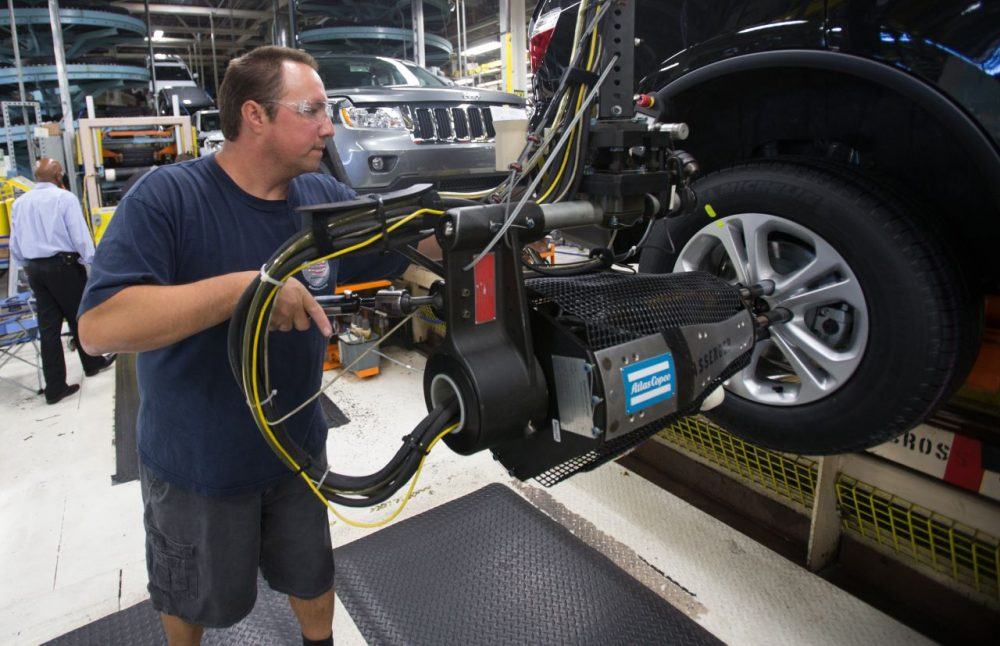 A worker mounts tires on a Chrysler SUV as it moves along the assembly line at the Jefferson North Assembly Plant in Detroit Michigan, August 7, 2012. (Geoff Robins/AFP/Getty Images)