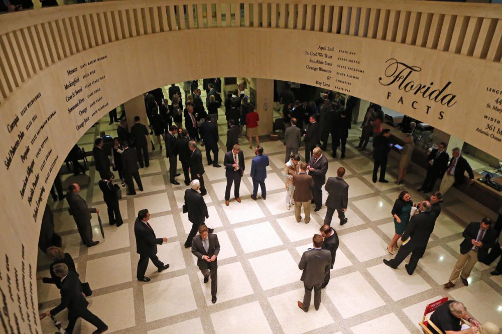 Lobbyists work in the rotunda between the Florida House and Senate chambers during session, Tuesday, April 28, 2015, at the Capitol in Tallahassee, Fla. The Florida House adjourned its annual session three days early because of a budget impasse with the Senate over Medicaid expansion. (Steve Cannon/AP)